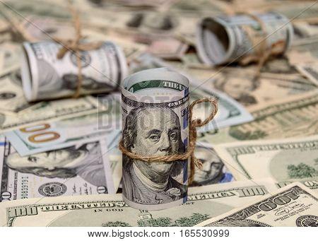 Hundred dollar bills rolled up on dollars background