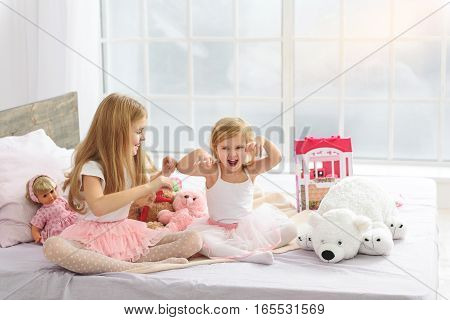 Cute female siblings are having fun at home. Little girl is roaring playfully as animal. Her elder sister is looking at her and smiling
