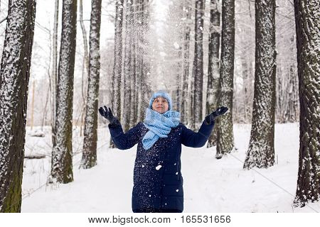 girl throws snow up in the grove with tall trees in winter