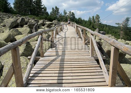 Wooden bridge across the moraines to the mountains