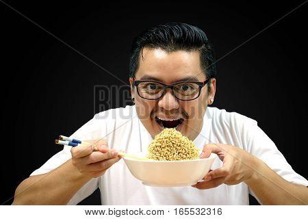 Asian man eating Instant noodles on black background