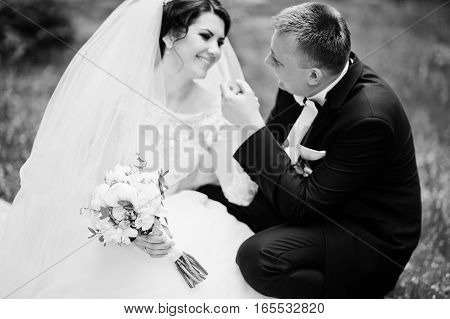 Wedding Couple Sitting On Green Grass And Looking Each Other. Black And White Photo