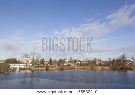 view over river Linge on dutch town of Leerdam in the netherlands under blue sky