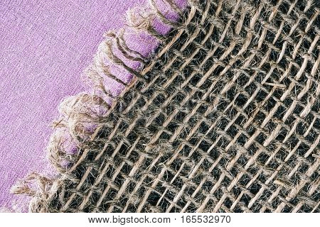 Combined background of lilac linen fabric and sackcloth. Macro view