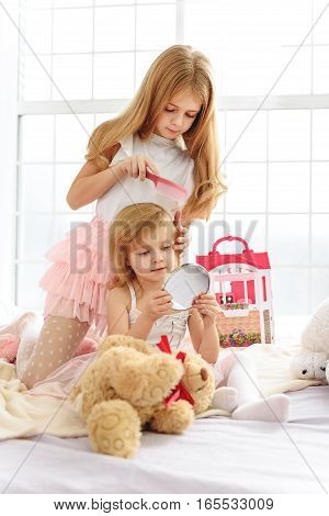 Confident girl is taking care of her small sister. She is combing her hair with concentration. Smiley child is looking at mirror while sitting on bed