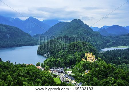 View of Hohenschwangau Castle and the town of Schwangau Germany with Lake Alpsee in the background.