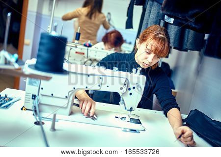 seamstress sews clothes. Workplace of tailor - sewing machine rolls of thread fabric scissors.