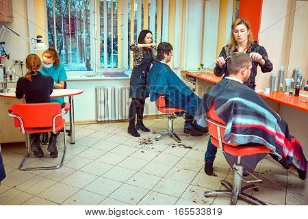 Smiling client sitting in a hair salon while hairdresser is combing her hair.