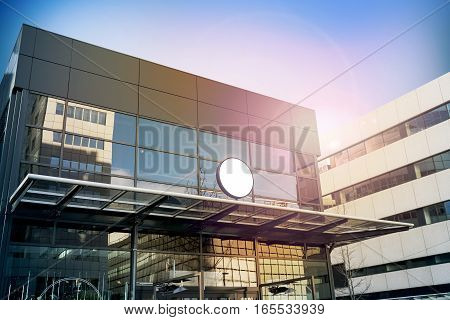 Blank white round signage mockup, modern business building. Circle sign board mock up hanging on glass roof of the store endrance. Street advertising banner design template.