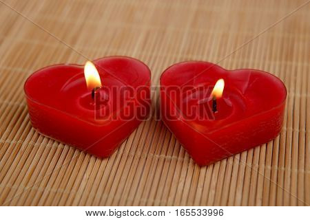 Heart shape candles. Two red candles burning on bamboo mat.