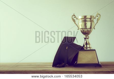 Graduation Cap With Champion Golden Trophy On Wood Table With Copy Space Ready For Your Design.gradu