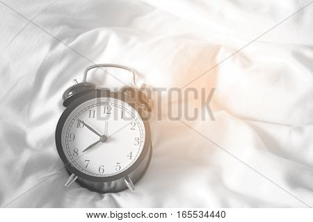 Alarm clock black style vintage place on a bed of white.