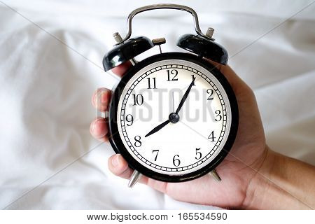 Vintage black clock in hand of man Eight hours 5 minutes