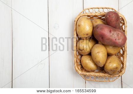 Raw potatoes with burlap on white wooden background, top view