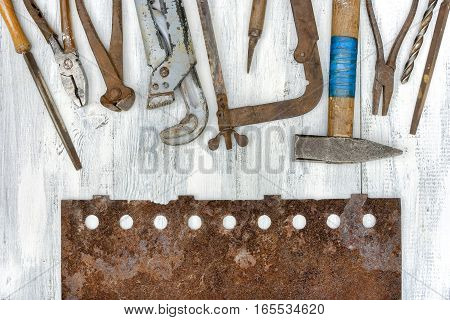 Old tools and rusty metal plate lying on a painted board