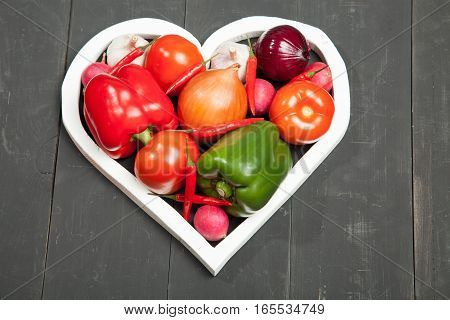 Vegetables in the heart. Peppers, tomatoes, garlic, eggplant, onions and radishes on a black background