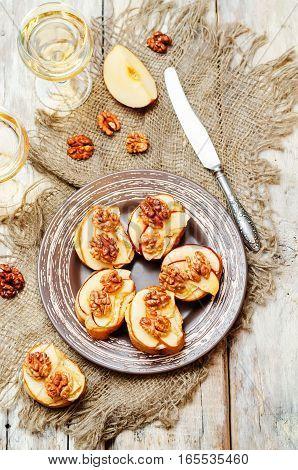 Apple Brie maple syrup walnut crostini on wood background