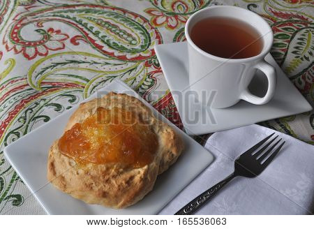 Nicely served single person breakfast of sweet pastry with fruit jam and a cup of hot tea on a colorful background