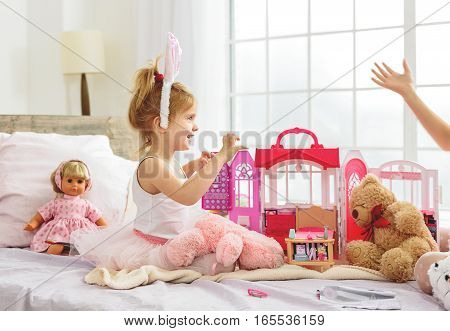 Cute little girl is playing with her elder sister at home. She is sitting on bed and laughing. Kid is wearing rabbit ears and raising hands playfully