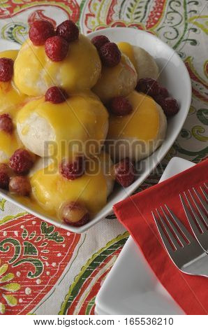 Nicely served Central European dessert (a version of Austrian Germknoedel) of steamed sweet dumplings with fruit filling and hot fruit sauce on a colourful background
