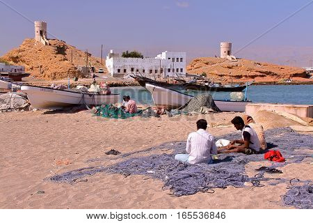SUR, OMAN - FEBRUARY 7, 2012: Fishermen at the Old Harbor in Ayjah