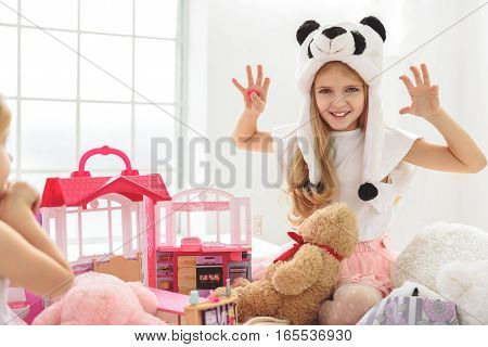 Joyful girl is roaring as if animal. She is sitting on bed and laughing. Her small sister is looking at her with interest