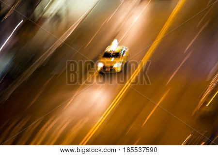 New York City taxi driving fast on city street at night blurred background NYC