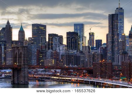NYC skyline at sunset with the night lights of the downtown skyscrapers and the Brooklyn Bridge in Manhattan New York City