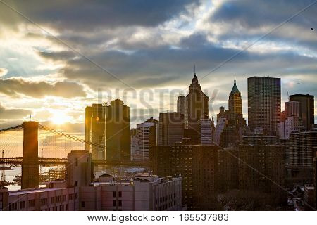 New York City skyline scene at sunset with a colorful view of the Brooklyn Bridge and Skyscrapers