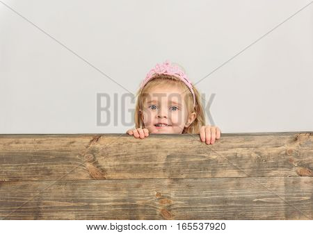 Curious little princess is peeping over wooden border and smiling. Isolated