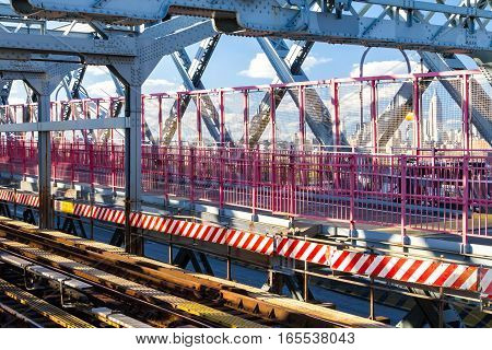 Scenic view of the Williamsburg Bridge subway tracks and pedestrian walkway with Manhattan skyline in background in New York City