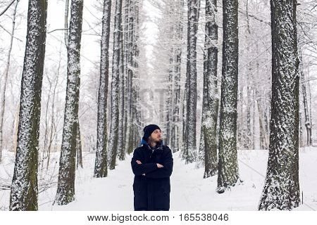 guy in the black jacket and hat standing in a snowy forest high