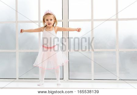 Pretty small princess is standing on windowsill and stretching arms sideways. Girl is looking at camera and smiling