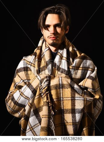 handsome bearded man covered in cozy checkered plaid and stylish hair on black studio background copy space