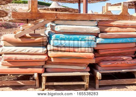 old sunbed mattresses stacked at Egyptian beach