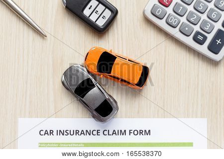 Top view of approved car insurance with car key car toy and calculator on wooden desk - accident concept