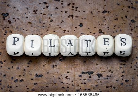 Pilates text on wooden cubes on a brown cork background