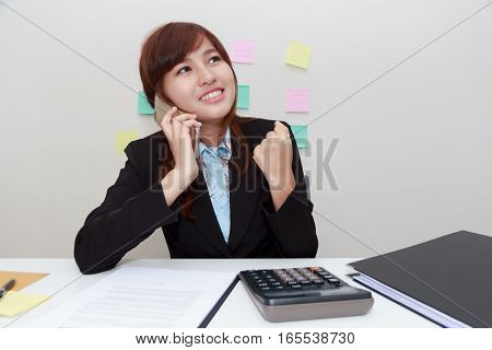 Excited or surprised business woman talking with someone on smart phone while sitting at her office