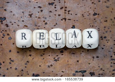 Relax text on wooden cubes on a brown cork background