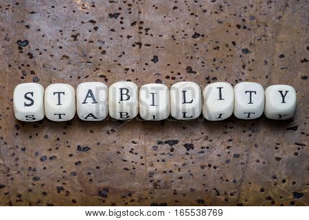 Stability Text On Wooden Cubes On A Brown Cork Background