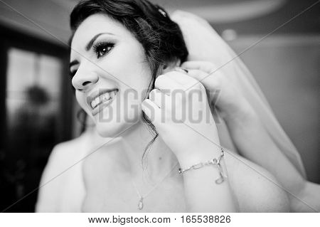 Close Up Hand Of Bridesmaid Who Helped Wear Earring For Bride At Wedding Morning Day. Black And Whit
