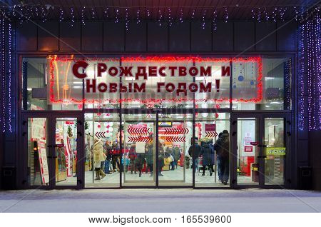 GOMEL BELARUS - JANUARY 5 2017: Unidentified people go to department store decorated with Christmas illuminations in evening shortly before Christmas Gomel Belarus