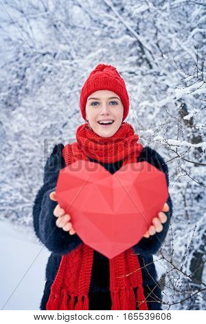 Love and valentines day concept. Excited woman showing giving red polygon paper heart shape over winter landscape. Shallow depth of field, focus on girl.