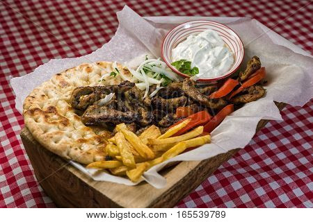 Homemade Greek meat gyros with tzatziki sauce, tomatoes and french fries