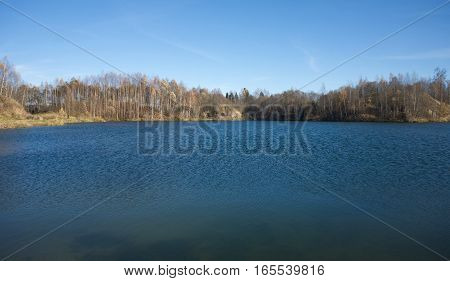 Beautiful Landscape with forest lake in autumn under clear blue sky
