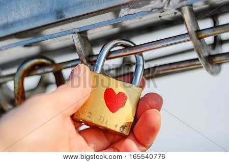 Old padlock with heart pattern on the palm. Checking the strength of the concept