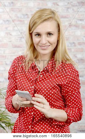 beautiful young blonde woman with red shirt and mobile phone