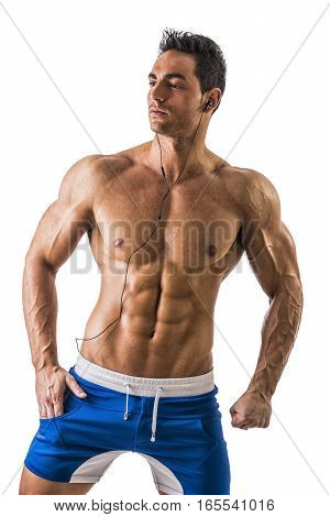 Attractive young man with muscular naked body listening to music with earphones, isolated on white background