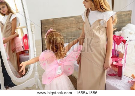 I am the real princess. Excited child is posing near mirror while wearing wings and crown. Her elder sister is trying on dress with interest
