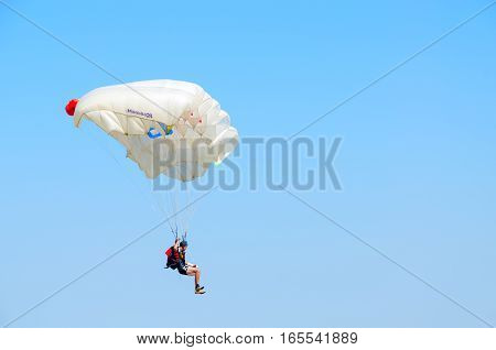 ZYABROVKA BELARUS - AUGUST 8 2015: Unknown man - skydiver with superimposed on forearm plaster cast performs jump on background of cloudless blue sky